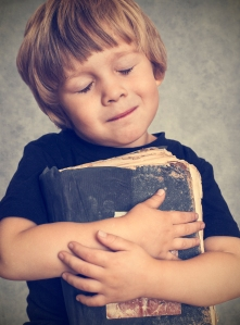 Little boy hugging an old book